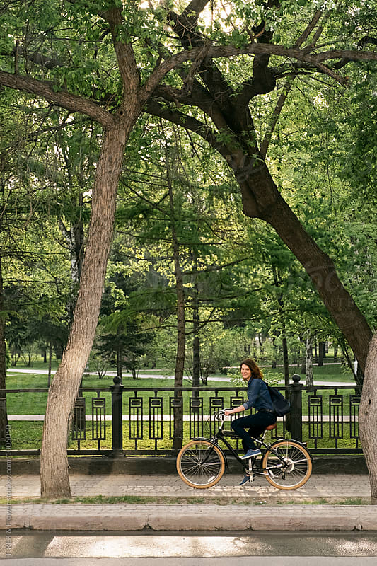 Smiling girl riding bike on sidewalk against of bright green park by Danil Nevsky for Stocksy United