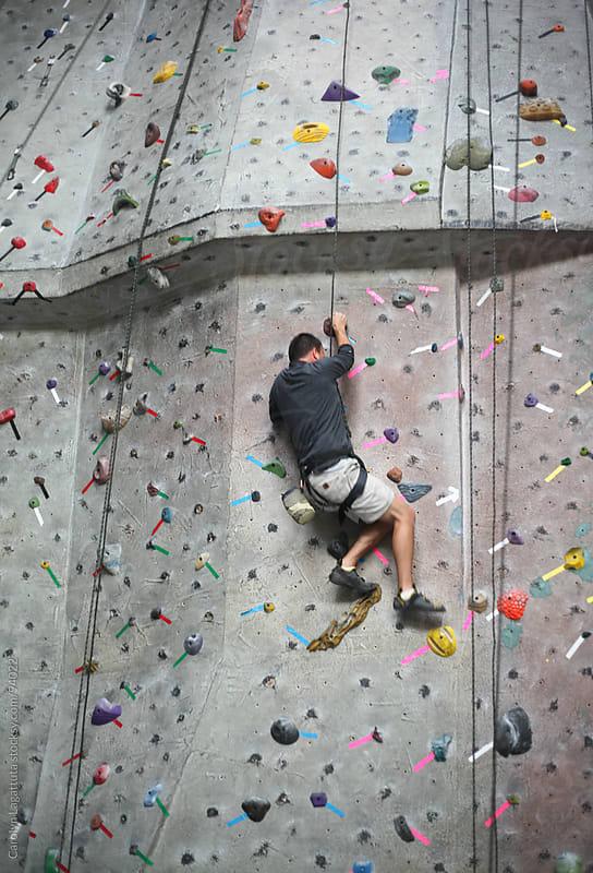 Male athlete climbing a rock wall by Carolyn Lagattuta for Stocksy United