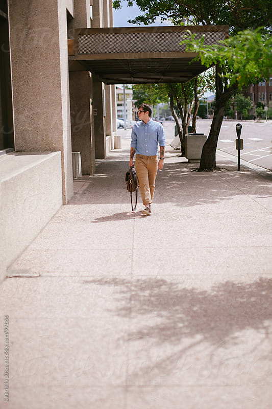 Young man walking downtown with briefcase  by Gabrielle Lutze for Stocksy United