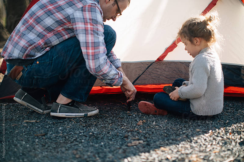 Father and daughter set up a tent on a camping trip by Meaghan Curry for Stocksy United
