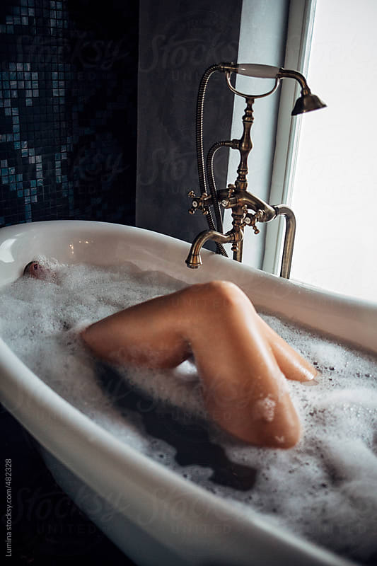 Legs of a Woman Lying in the Bathtub by Lumina for Stocksy United