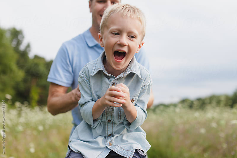 A father and son playing and laughing outdoors by Amanda Worrall for Stocksy United