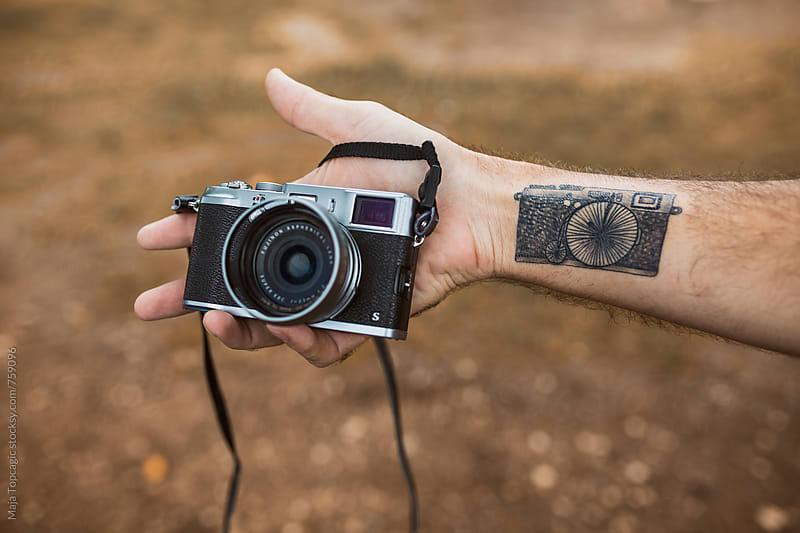 A man with a camera tattoo holding a camera by Maja Topcagic for Stocksy United