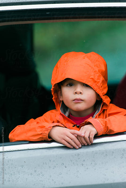 child in orange raincoat looking outside an open car window, vertical by Tara Romasanta for Stocksy United