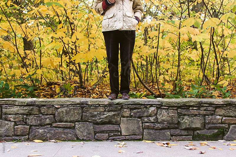 Woman stands in front of yellow leaves. by Holly Clark for Stocksy United