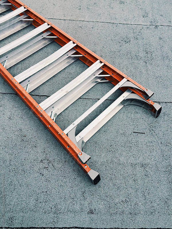An orange ladder on concrete floor by Murtaza Daud for Stocksy United