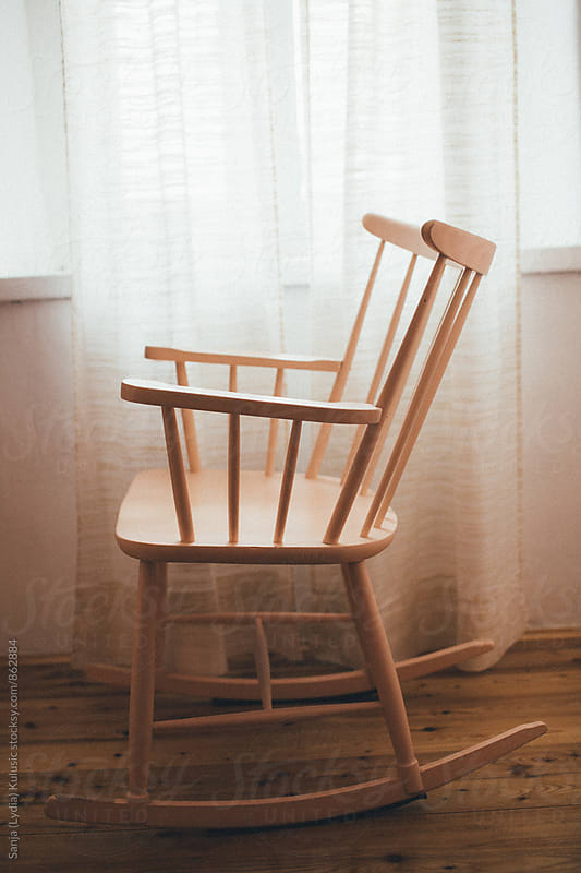 Rocking chair under the window with pretty backlight by Sanja (Lydia) Kulusic for Stocksy United