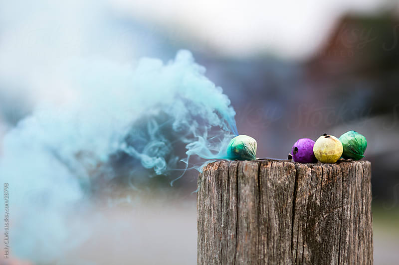 Burning Smoke Bombs Sitting on Fence on the Fourth of July by Holly Clark for Stocksy United
