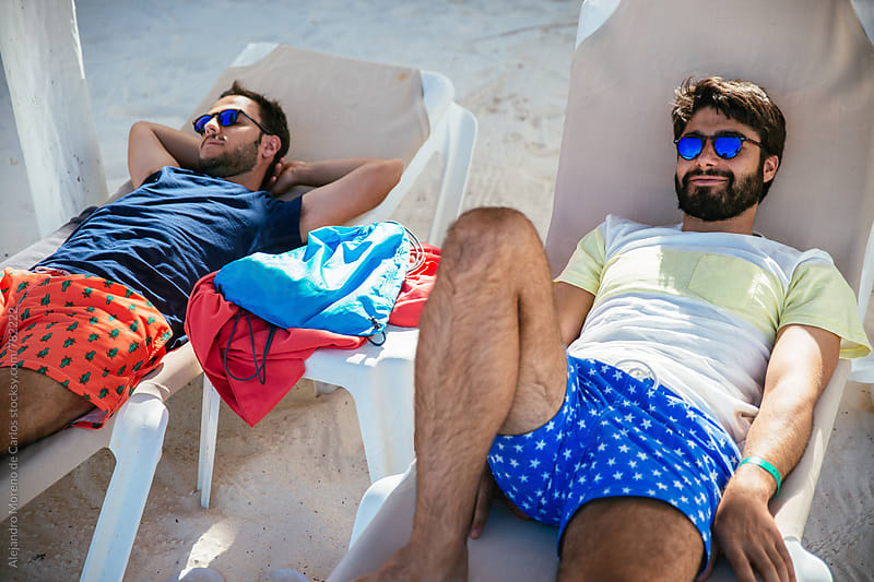 Two men in swimming trunks relaxing on beach chairs by Alejandro Moreno de Carlos for Stocksy United