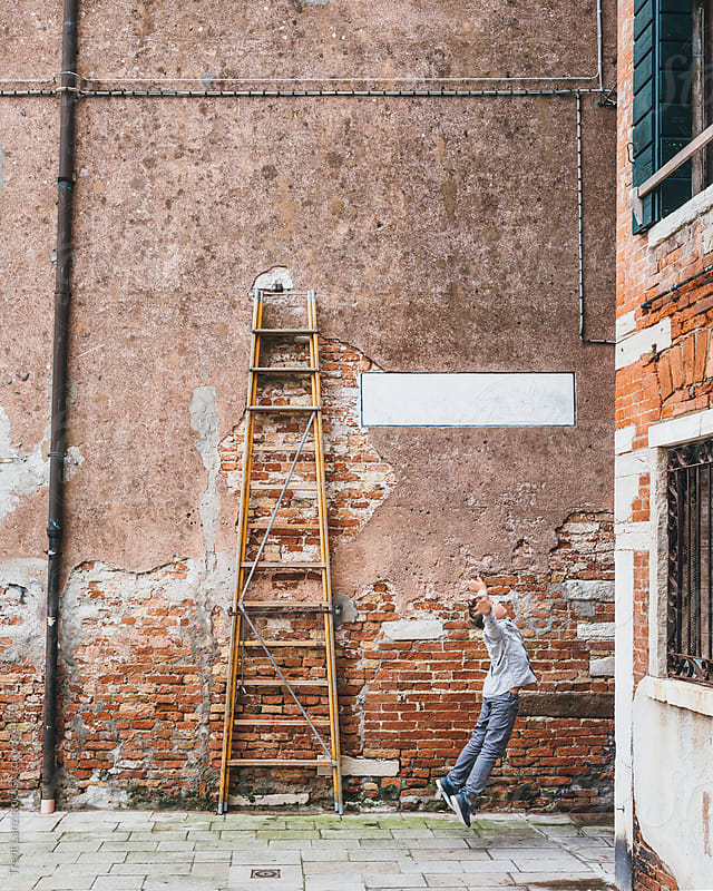 Kid jumping on street against brick wall in Venice by Trent Lanz for Stocksy United