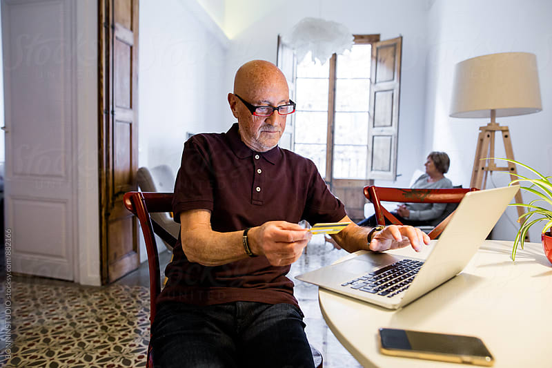 Elderly man shopping online on his laptop at home. by BONNINSTUDIO for Stocksy United