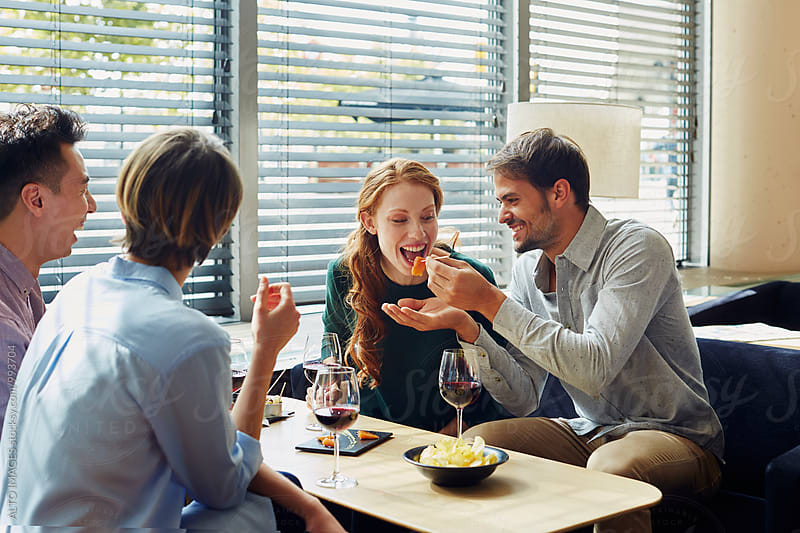 Friends Looking At Man Feeding Woman In Restaurant by ALTO IMAGES for Stocksy United