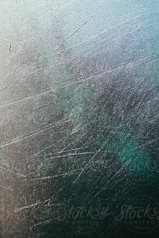 Metallic silver paint in scratched plastic surface, close up by Paul Edmondson for Stocksy United