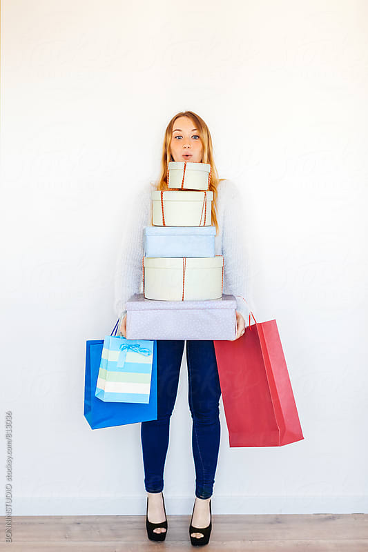 Blonde woman holding a stack of Christmas gifts. by BONNINSTUDIO for Stocksy United