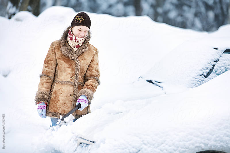 Young woman cleaning car from snow by Ilya for Stocksy United