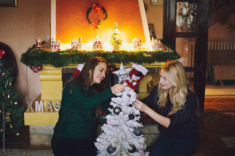 Two female friends preparing Christmas tree by Jovana Rikalo for Stocksy United