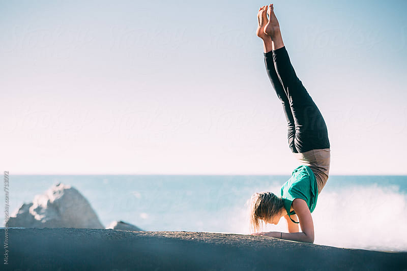 Fit young woman doing yoga on a rocky beach by Micky Wiswedel for Stocksy United