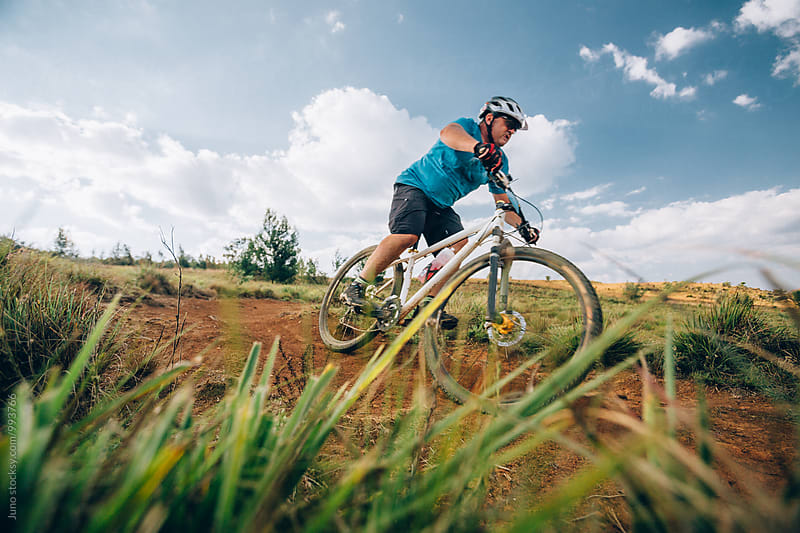 Mountain biker riding on a dirt track by Micky Wiswedel for Stocksy United