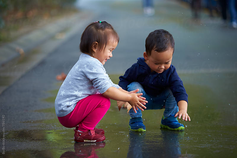 two lovely little kids playing on wet road by Bo Bo for Stocksy United