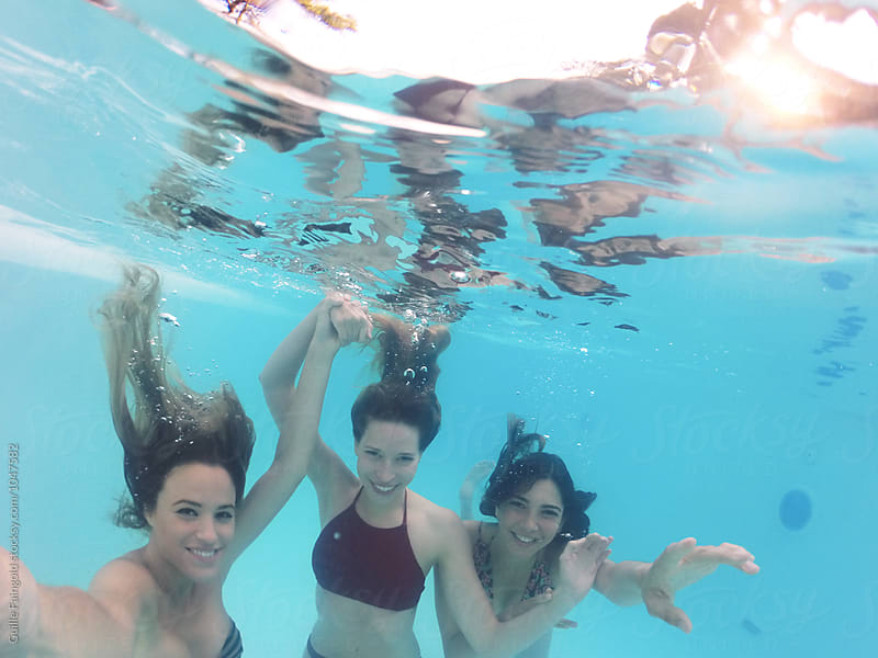 Three friends in bikini swimming in pool underwater by Guille Faingold for Stocksy United