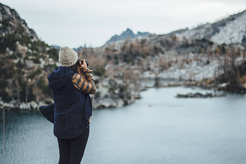 Woman takes picture of blue lake below by Tari Gunstone for Stocksy United