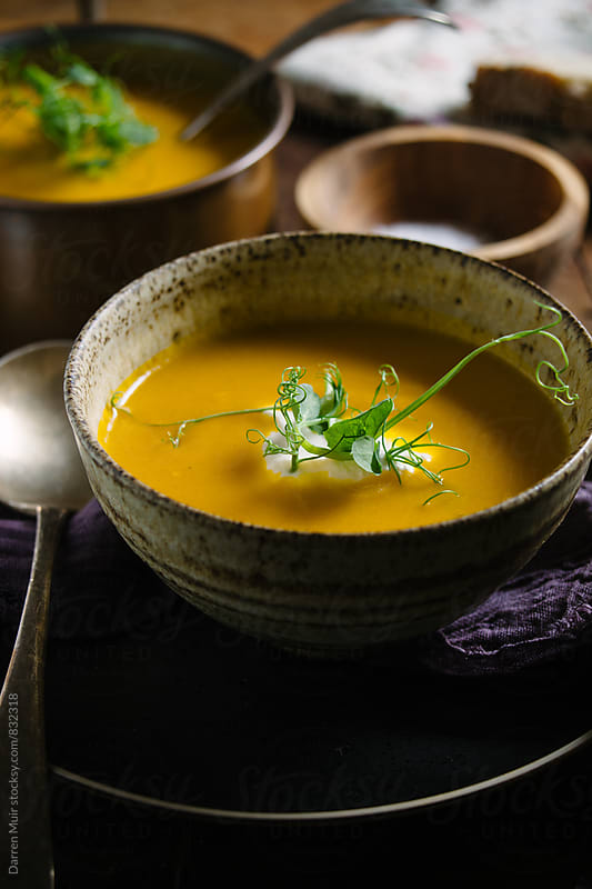 A bowl of carrot soup. by Darren Muir for Stocksy United