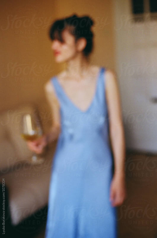 Out-of-focus shot of woman with a glass of wine by Lyuba Burakova for Stocksy United