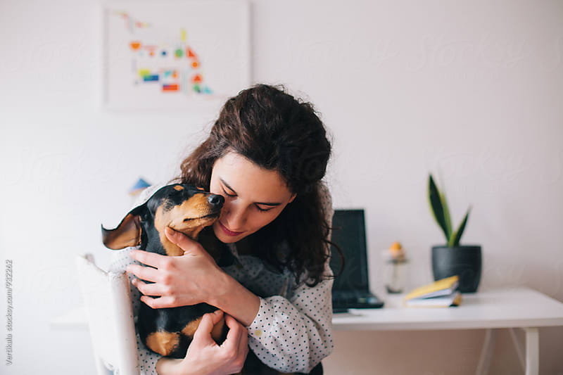 Brunette woman hugging her small black dog indoor by Marija Mandic for Stocksy United