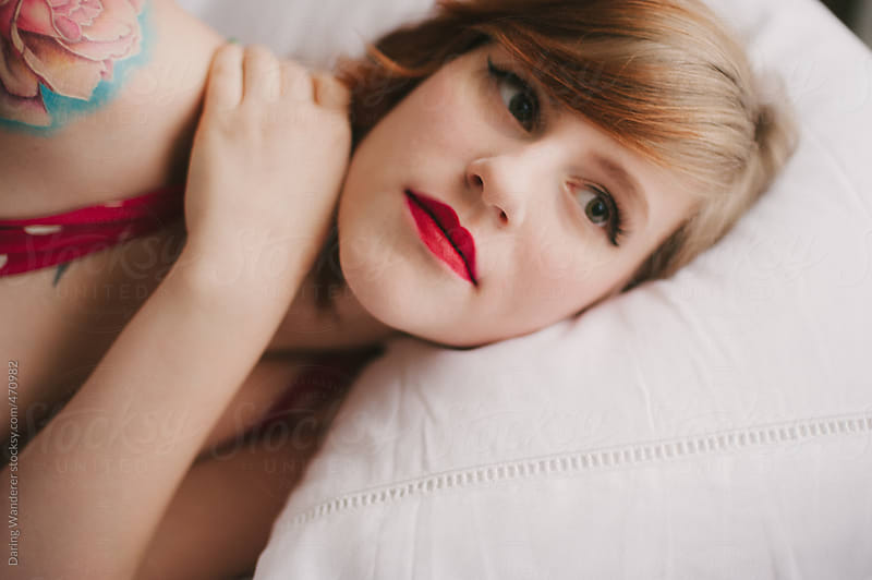 Young woman with flower tattoo lying on bed wearing bright red lipstick by Daring Wanderer for Stocksy United