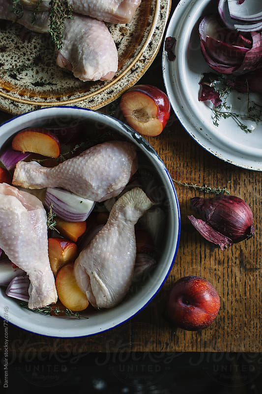Preparing a chicken meal, with plums thyme and red onion. by Darren Muir for Stocksy United