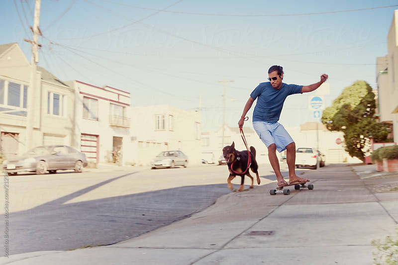 Man Walking Dog by Street Skateboarding by Joselito Briones for Stocksy United
