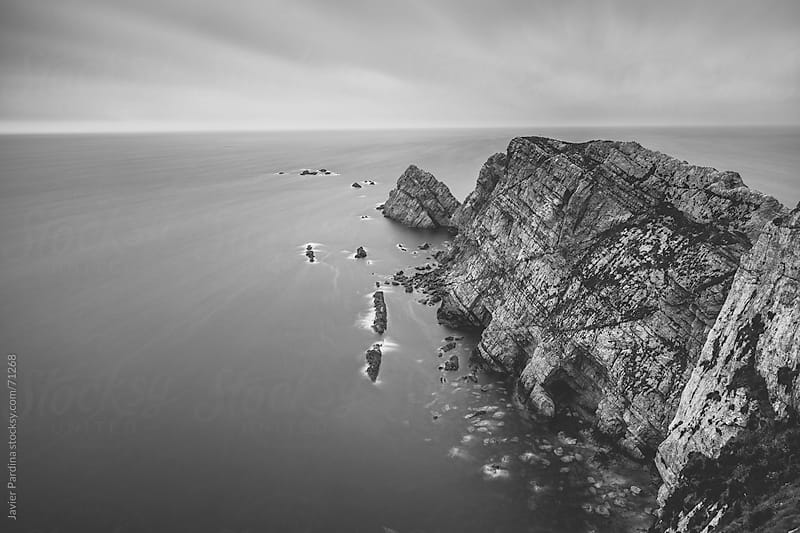 Cloudy day at the beach with long exposure in black and white by Javier Pardina for Stocksy United