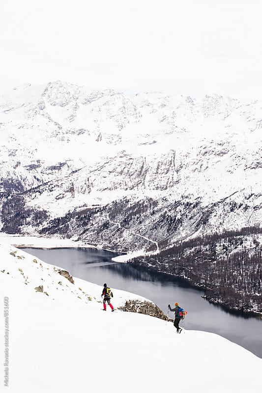 Two hikers walking in an alpine landscape by michela ravasio for Stocksy United