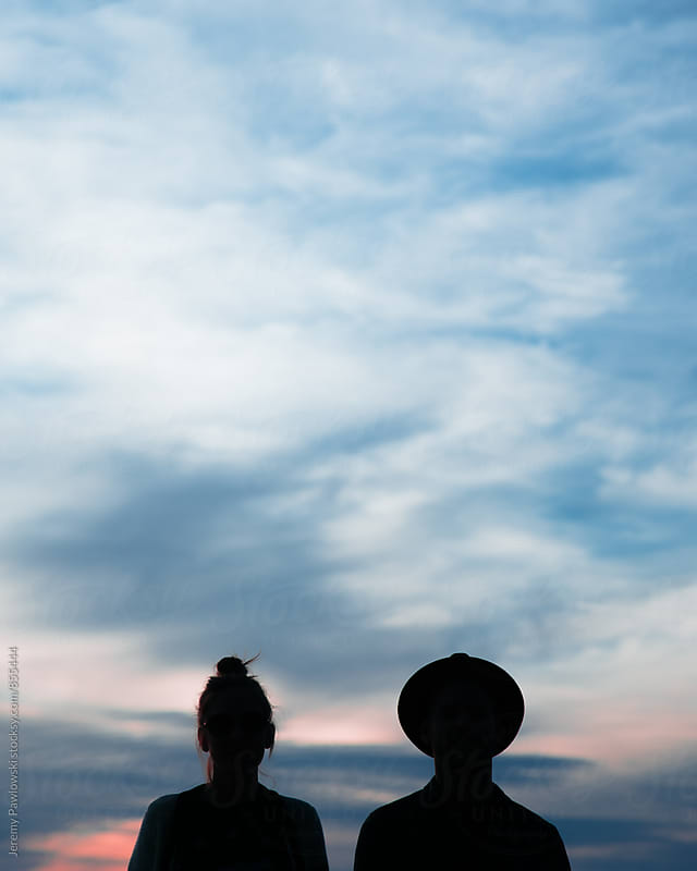 Silhouette of couple with clouds and sunset. by Jeremy Pawlowski for Stocksy United