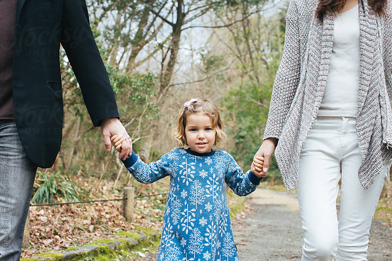 Portrait of Little Cute Girl Holding Her Parents' Hand by Julien L. Balmer for Stocksy United