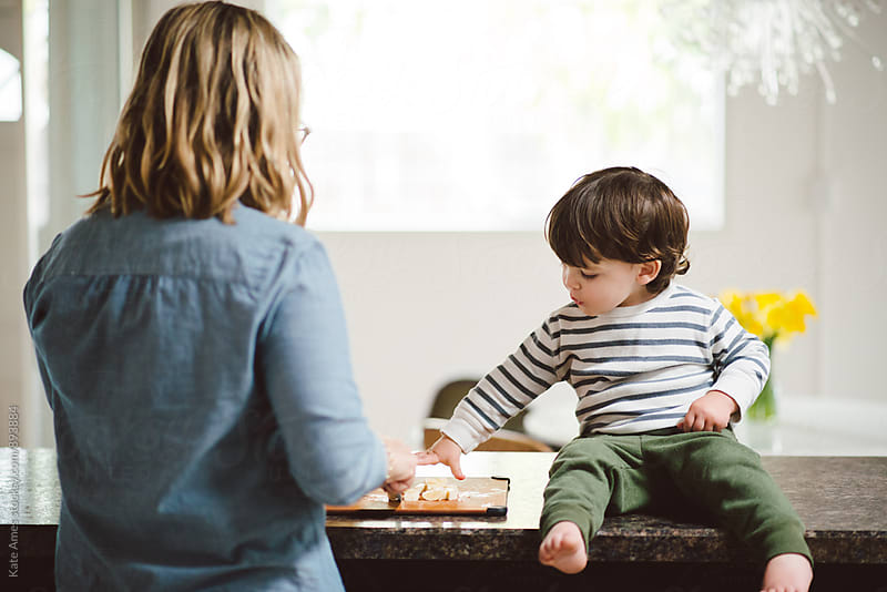 Young toddler sitting on counter eating fruit with his mother by Kate Daigneault for Stocksy United