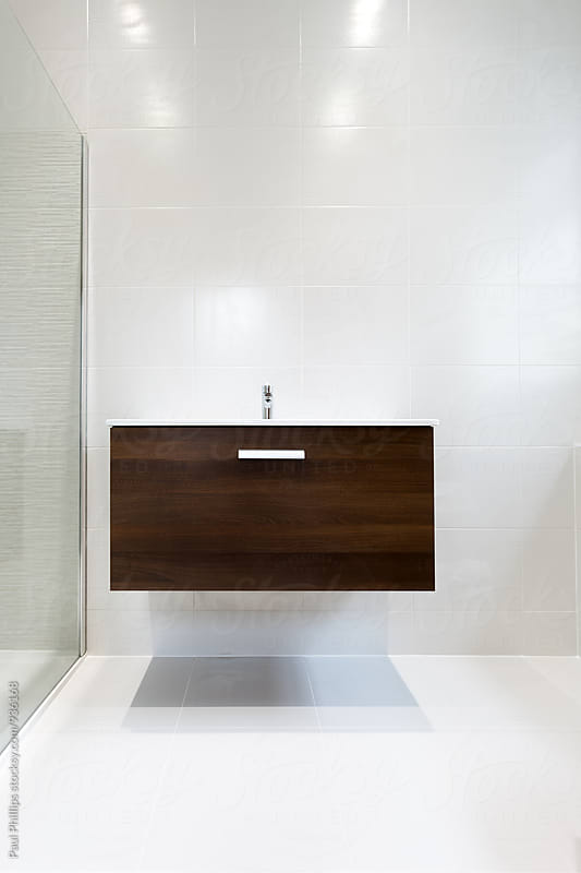 Wall hung vanity unit with sink in a contemporary shower room. by Paul Phillips for Stocksy United
