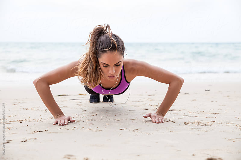 Woman doing pushups at the beach - fitness outdoors  by Jovo Jovanovic for Stocksy United