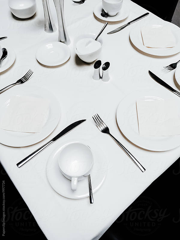 Empty restaurant table with plates and cutlery by Paperclip Images for Stocksy United