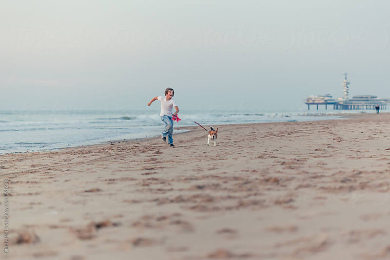 Boy running on the beach with a beagle dog on a leash by Cindy Prins for Stocksy United