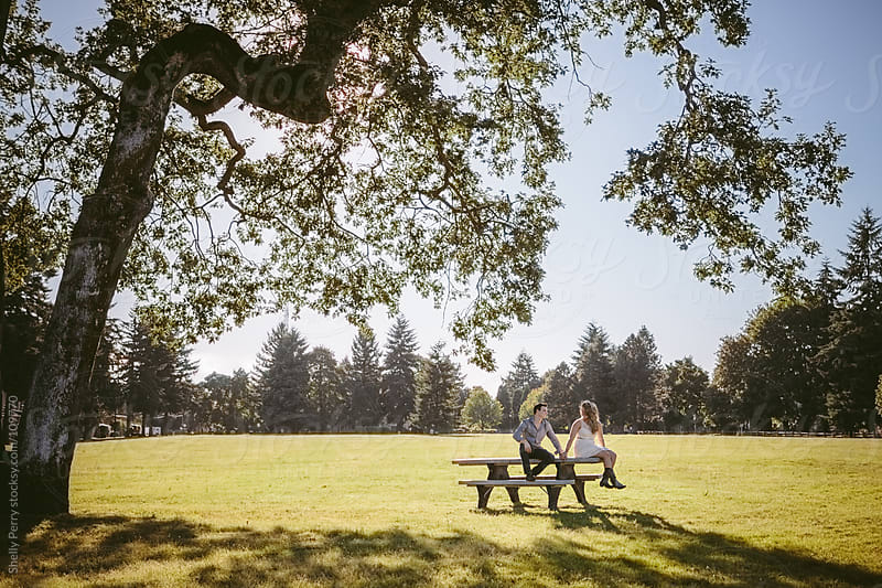 Young couple sitting on a picnic table  by Shelly Perry for Stocksy United