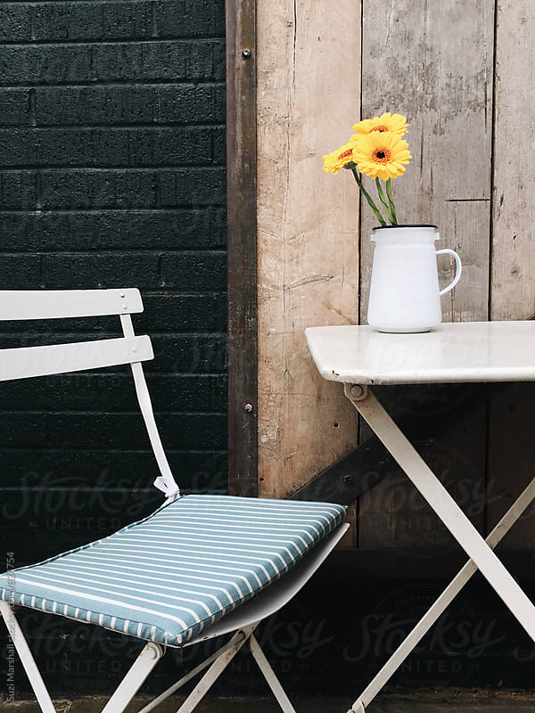 Chair and table with flowers outside a cafe by Suzi Marshall for Stocksy United
