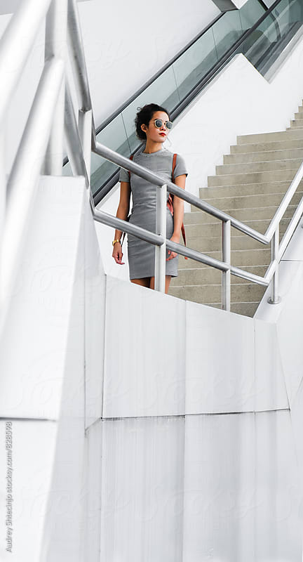 Attractive young woman at sterile white space/staircase by Audrey Shtecinjo for Stocksy United