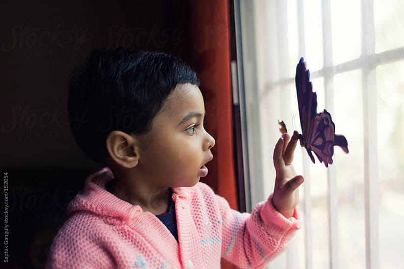 Toddler touching a toy butterfly on a glass window pane by Saptak Ganguly for Stocksy United