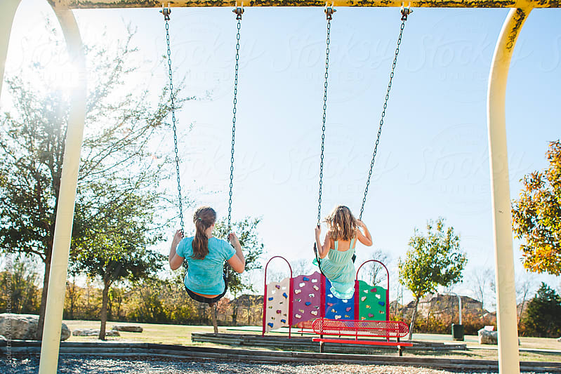 Girls on the swings by Courtney Rust for Stocksy United