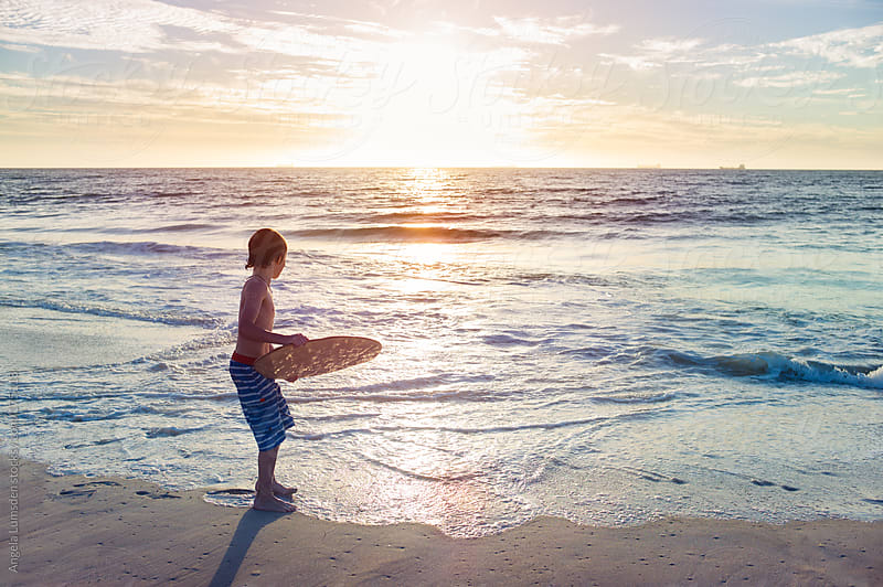 Boy skim boarding at sunset by Angela Lumsden for Stocksy United