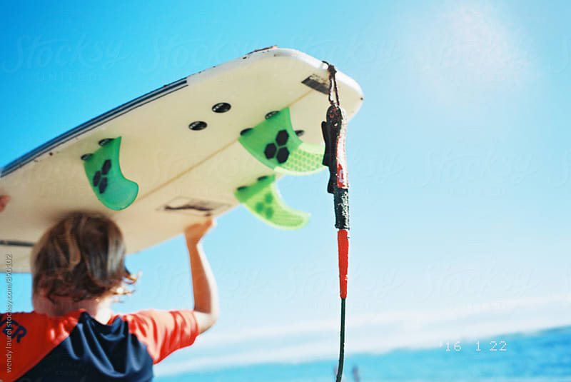 boy carrying surfboard on his head against bright blue sky by wendy laurel for Stocksy United