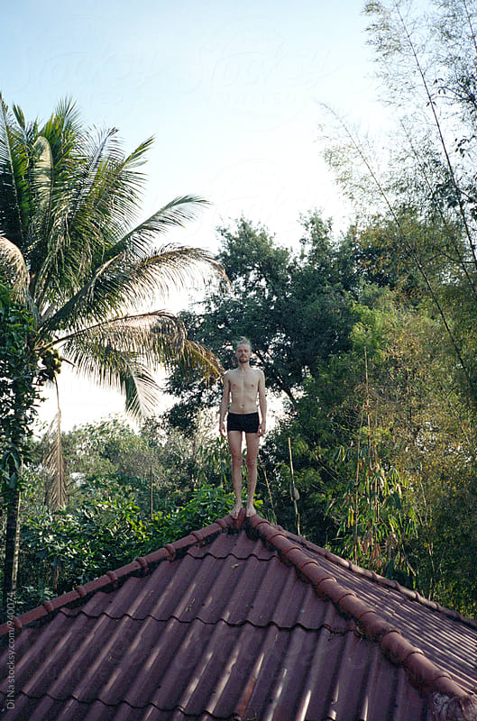 Young man stands on the roof of the house with tropics on the background by Dina Lun for Stocksy United