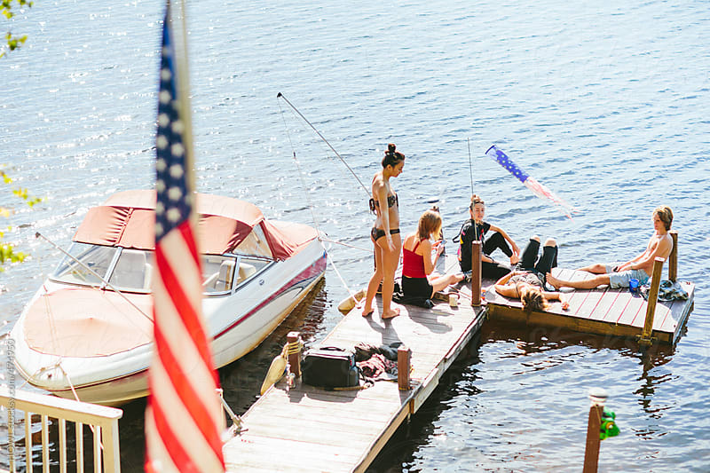 A group of friends are hanging on the dock during a summer afternoon by HOWL for Stocksy United