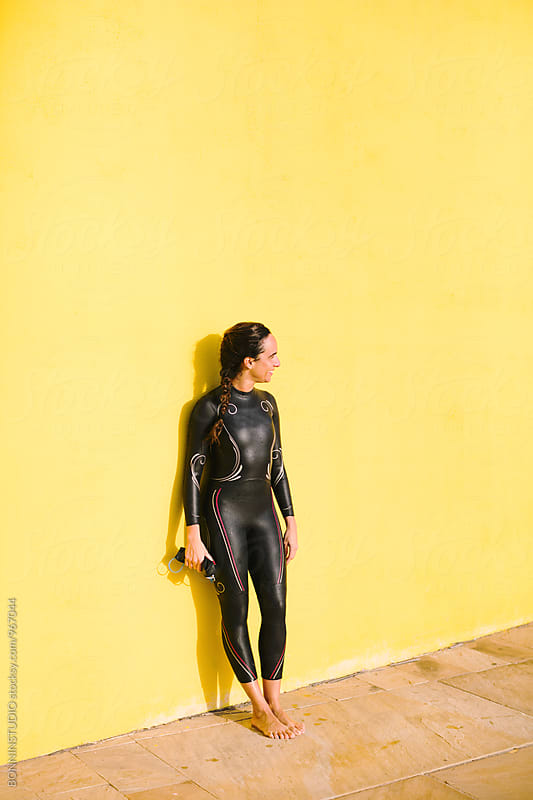 Woman wearing a wetsuit standing in front of a yellow wall. by BONNINSTUDIO for Stocksy United
